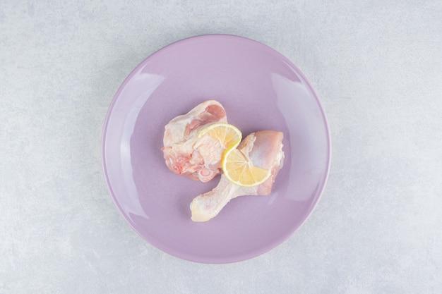 Carne de pollo y limón en el plato, sobre la superficie de mármol