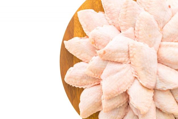 Carne de pollo sin procesar y el ala en tabla o placa de madera de corte