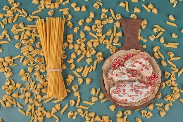 Carne de pollo sobre una tabla de madera con pasta y semillas de granada, vista superior.