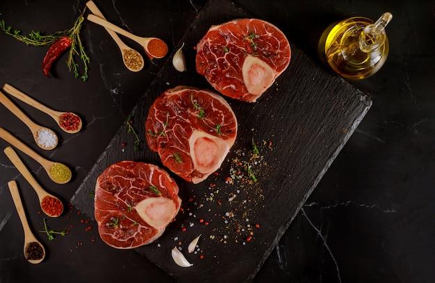 Carne de res cruda y especias para preparar el plato de ossobuco en negro vista superior.