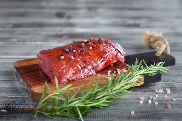 Carne de res entera filete de solomillo crudo fresco, romero, pimienta, sal marina sobre tabla de cortar de madera