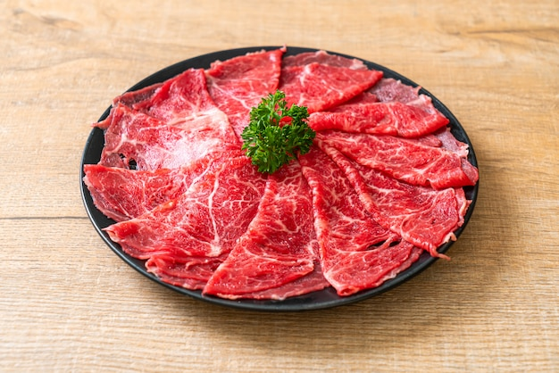 Carne de res fresca cruda en rodajas con mármol