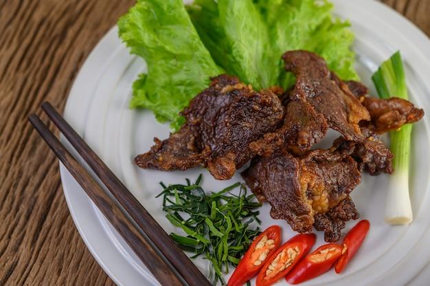 Carne de res frita comida tailandesa en un plato blanco con cebolleta, hojas de lima kaffir, chiles, palillos, ensalada y pasta de chile en una taza.