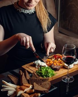 Carne de res frita con verduras sobre tabla de madera