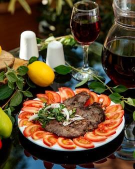 Carne de res marinada servida con rodajas de tomate, cebolla y cilantro