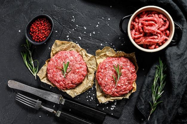 Carne de res molida cruda hamburguesa chuletas de carne y condimentos. granja de carne orgánica. fondo negro. vista superior