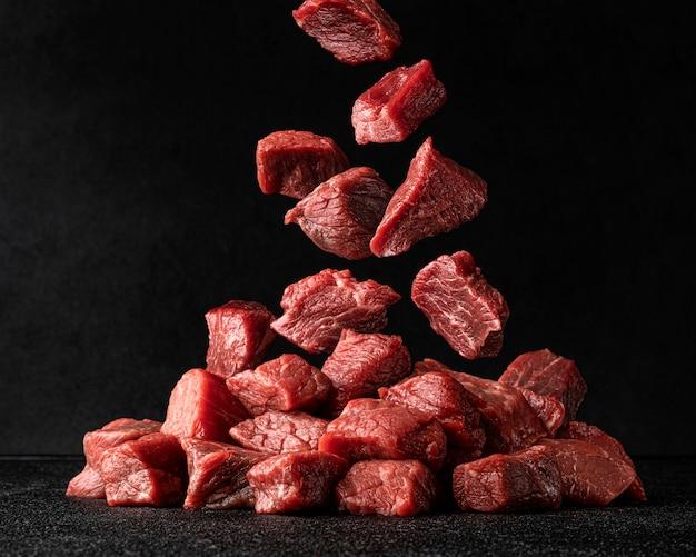 Carne de res en rodajas, cubos de carne cruda cayendo sobre fondo negro