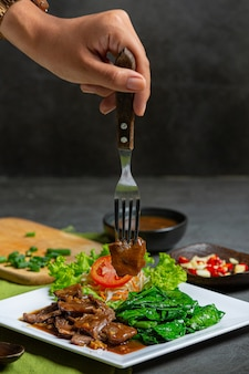 Carne de res sofrita en salsa de ostras y servida.