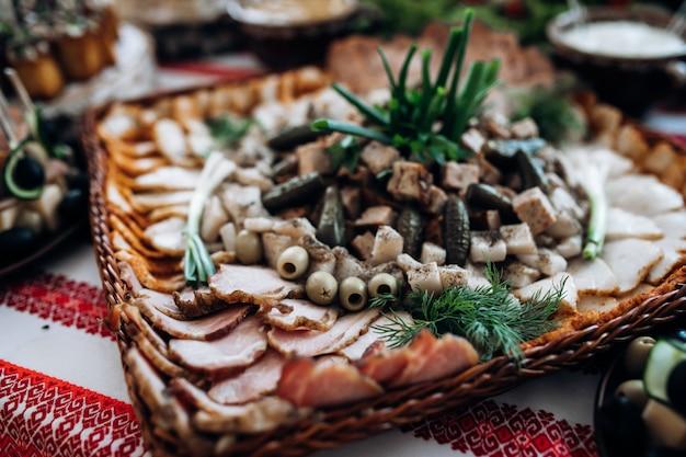Carne en rodajas y otros bocadillos están en la mesa de celebración