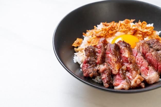 Carne en rodajas en un tazón de arroz cubierto con huevo
