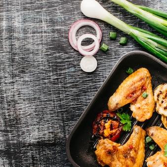 Carne sabrosa frita en sartén con cebolla en mesa de madera