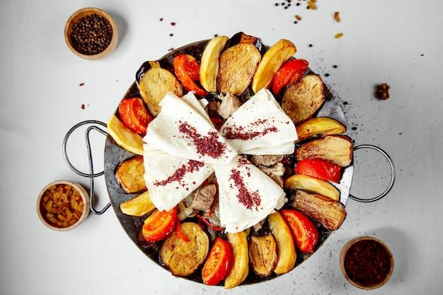Carne saj con patatas berenjenas y pan de pita espolvoreado con zumaque