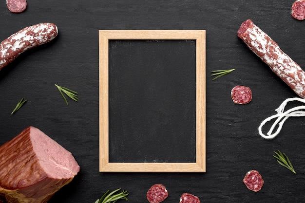 Carne de salami y filete con marco en el escritorio