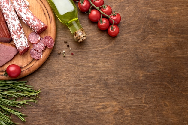 Carne de salami y filete sobre tabla de madera con espacio de copia