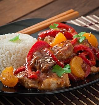 Carne en salsa picante, pimiento dulce y mandarinas con guarnición de arroz hervido