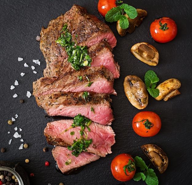 Carne de ternera rústica jugosa con especias y verduras asadas. vista superior