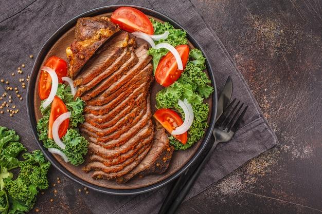 Carne de vaca cocida picante con la ensalada de la col rizada en placa negra en fondo oscuro.