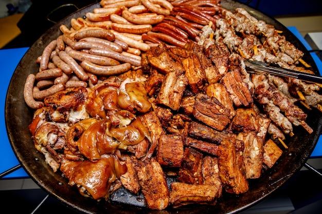 Carne variada. salchichas asadas, costillas, pierna en una sartén grande.