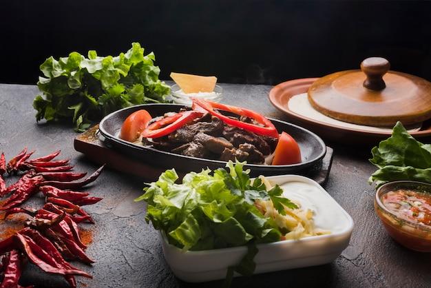 Carne, verduras y aperitivo en mesa de madera.