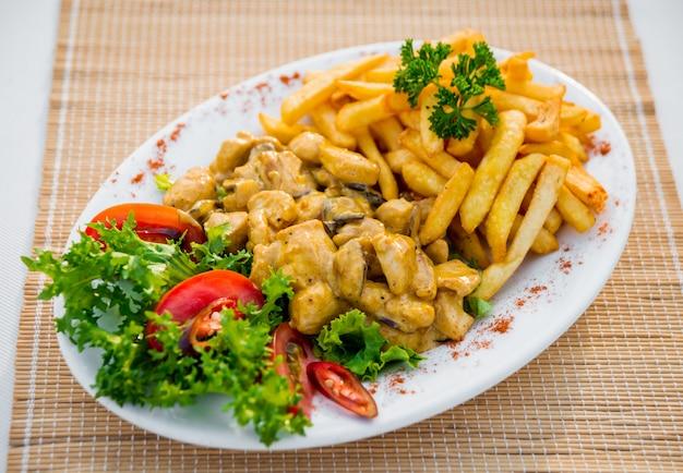 Carne con verduras en un plato blanco. restaurante.