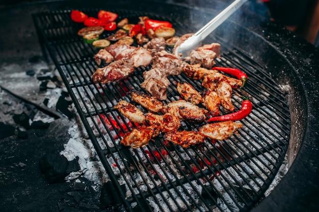 Carnes a la brasa en barbacoa con llamas y brasas