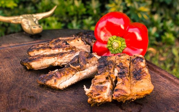 Carnes a la brasa y pimiento rojo sobre mesa.
