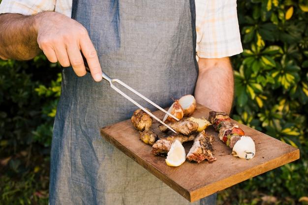 Carnes a la brasa y sabrosas verduras en escritorio de madera en las manos.