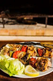 Carnes a la brasa y verduras en brochetas.