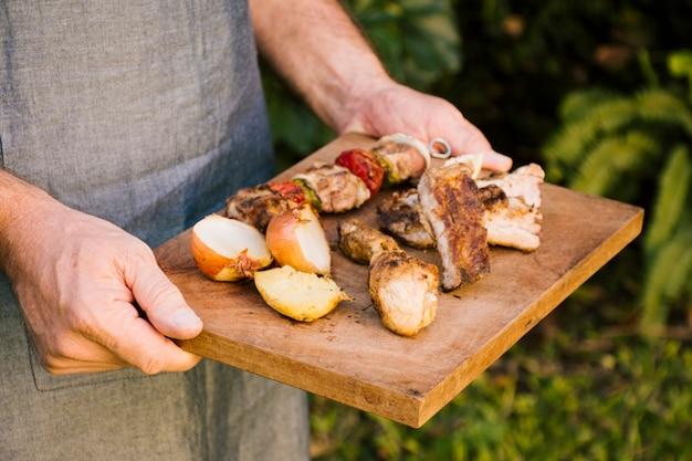 Carnes a la brasa y verduras en escritorio de madera en las manos.