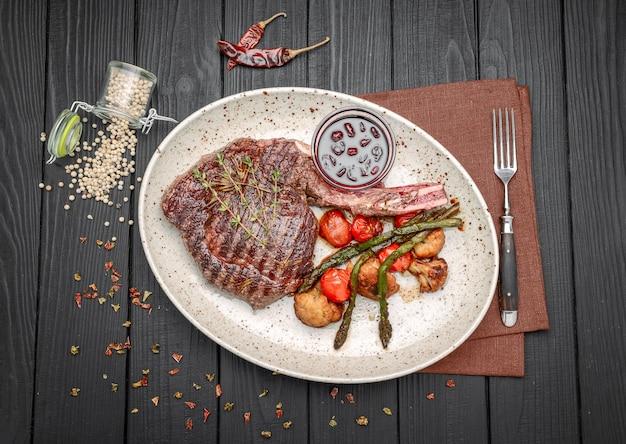 Carnes a la brasa y verduras en la mesa de madera rústica