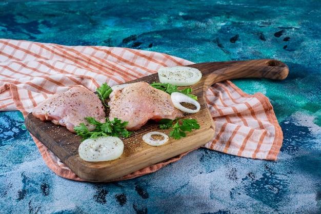 Carnes de pollo en una tabla para cortar sobre el paño de cocina