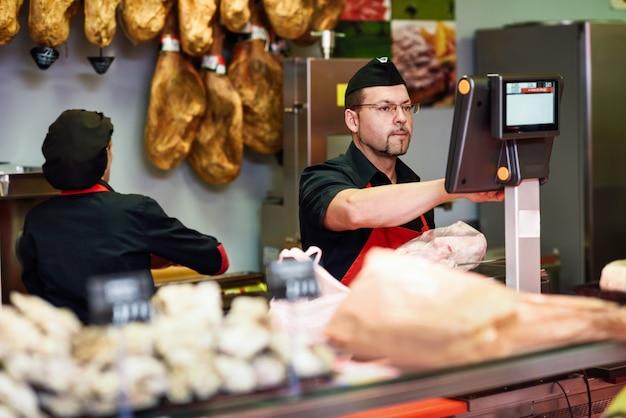 Carnicero en una carnicería pesando la carne y cargando.
