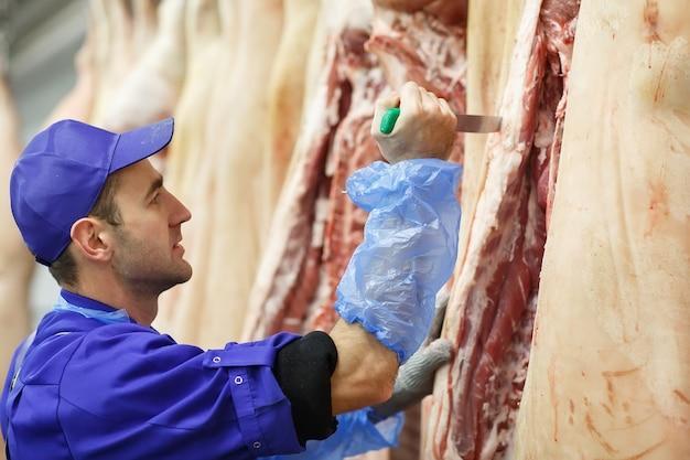 Carnicero cortando carne de cerdo en la fabricación de carne.
