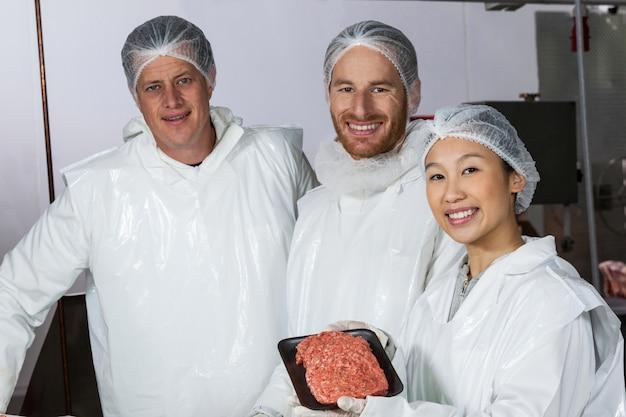 Carnicero con empanadas de carne cruda dispuestas en bandeja