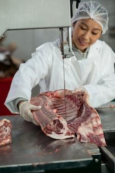 Carnicero hembra cortando carne cruda en una sierra de cinta