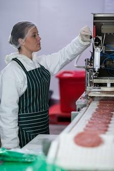Carnicero hembra procesando hamburguesas