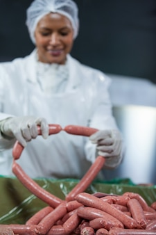 Carnicero hembra procesando salchichas