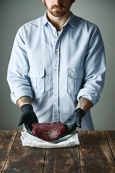 Carnicero hipster barbudo con guantes negros ofrece un trozo de filete de carne de ballena
