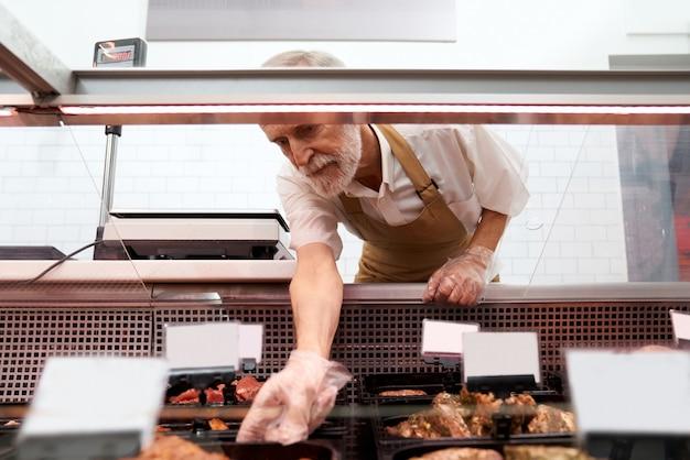 Carnicero macho sacar carne cruda de mostrador.