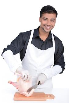 Carnicero profesional en delantal sonriendo y cocinando pollo.