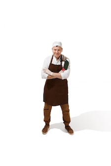 Carnicero sonriente posando con una cuchilla aislada
