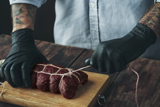 Carnicero tatuado irreconocible en guantes negros ata un trozo de carne con una cuerda artesanal para fumarlo en madera