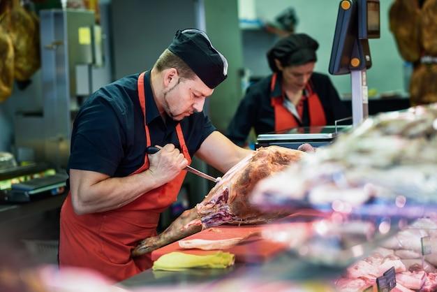 Carniceros deshuesando un jamón en una carnicería moderna