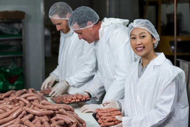 Carniceros empacando salchichas crudas