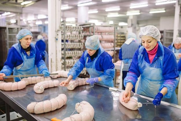 Carniceros procesando salchichas en la fábrica de carne.