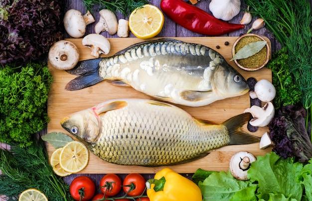 Carpa y carpa espejo en una tabla de cortar rodeada de verduras. pescado fresco antes de cocinar con verduras