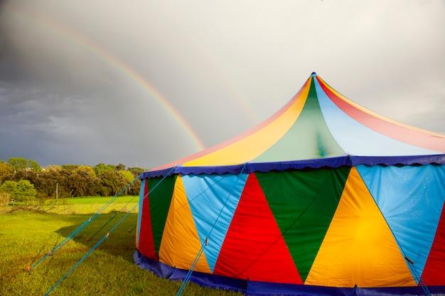 Carpa de circo de colores en un día lluvioso con un arco iris en el cielo