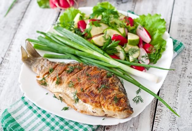 Carpa frita de pescado y ensalada de vegetales frescos