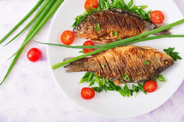Carpa frita de pescado y ensalada de verduras frescas. endecha plana. vista superior