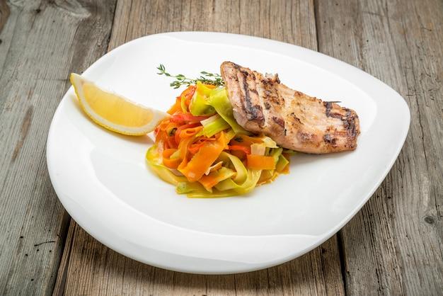 Carpa de pescado frito y ensalada de verduras frescas sobre fondo de madera.